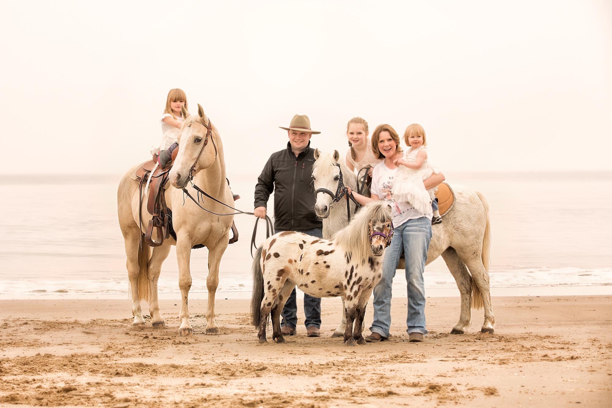 Familie mit Kindern und Pferden am Meer